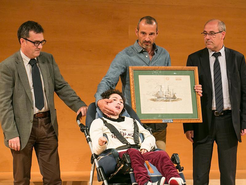 Foto : José Ferré rep el Premi LiberPress Camins, que li fan a mans Jordi Serra i Albert Falgueras, de l¿Associació Catalana de la Síndrome de RETT.